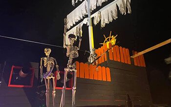 The backside of the pirate ship includes a skeleton forcing another skeleton to walk the plank, cannons, orange fencing, the captain's wheel and one of the masts.