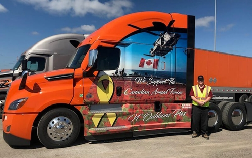 Michael Cunningham, Schneider's 2020 Canada Ride of Pride driver, poses in front of his new Ride of Pride truck. The truck is decked out in various decals to honor those who serve past and present.