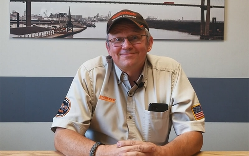 Brian Johnson is seated and smiling in his Training Engineer uniform.