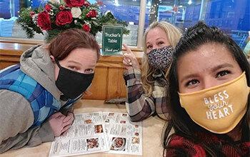 """Three women who are wearing masks, sit at a table at a restaurant with menus in front of them. One of the women points at a sign that says """"Trucker's Table."""""""