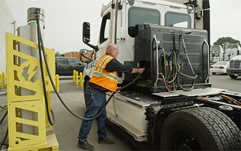 A bald truck driver wearing a safety vest, black shirt and jeans plugs the eCascadia semi-truck into the charging station.