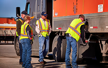 A truck driver trainer demonstrates how to use the trailer landing gear.