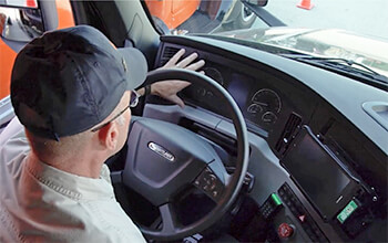 Driving Instructor Brett waves his hand in front of the odometer of a 2021 Freightliner Cascadia semi-truck.