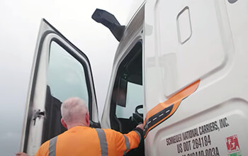 A driver wearing a reflective orange long sleeved shirt opens the door of a white Schneider semi-truck with MirrorEye cameras instead of standard mirrors.