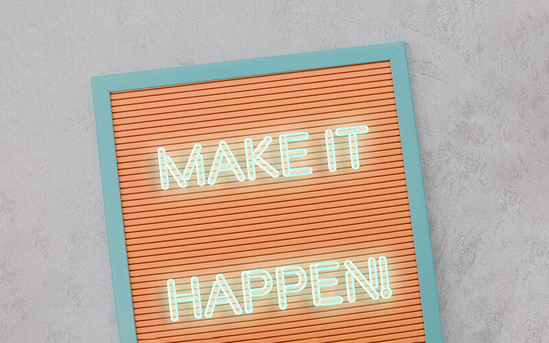 A brown letter board with light blue trim has the saying, 'Make it happen' on it in neon white lettering.