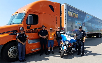 Schneider tractor-trailer with driver and police officer
