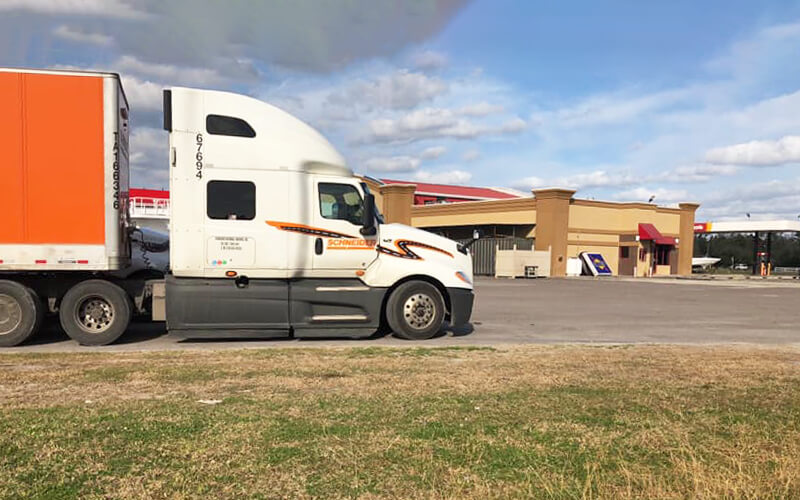 A Schneider semi-truck is parked outside of a truck stop.