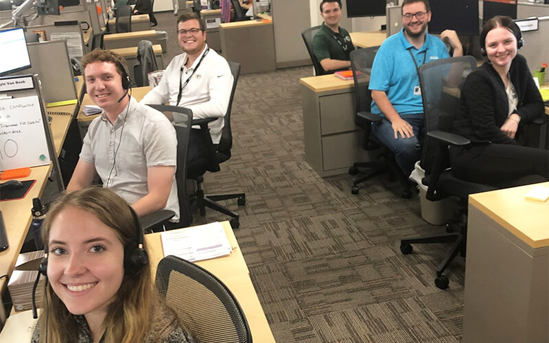 In an office setting are six recruiters who are wearing headsets and sitting at their desks.