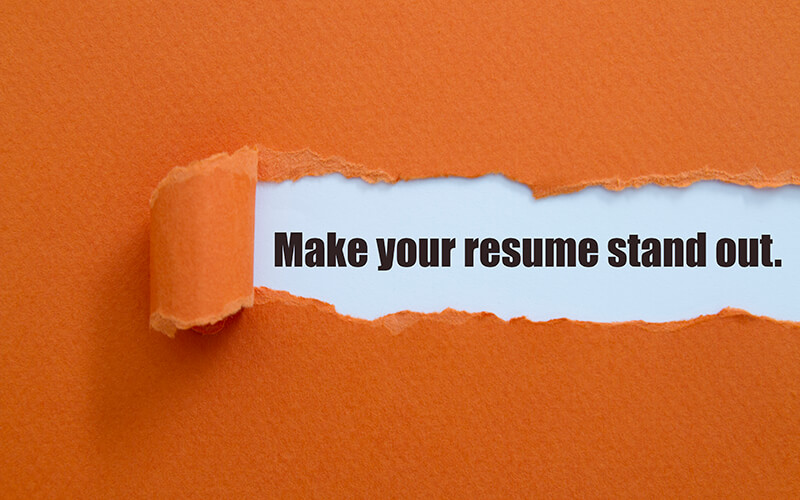 """A piece of orange paper is ripped out of a larger piece of orange paper and within the ripped part are the words, """"Make your resume stand out."""""""