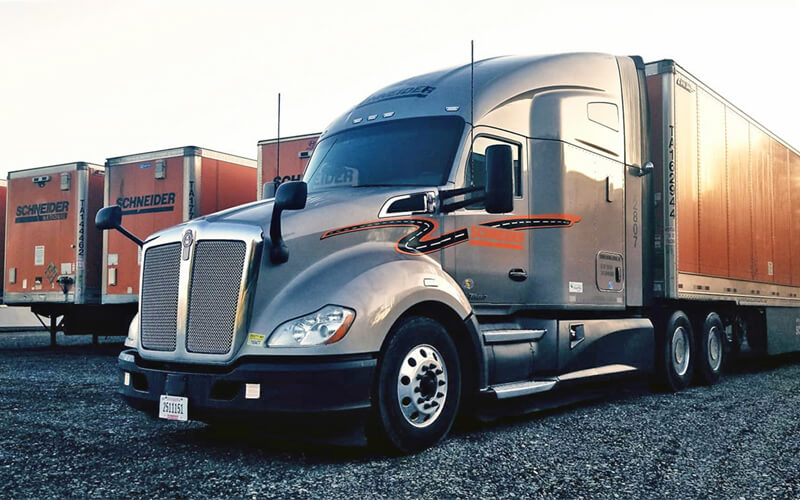 A grey Schneider Kenworth truck with an orange Schneider trailer is parked within a row of other orange Schneider trailers.