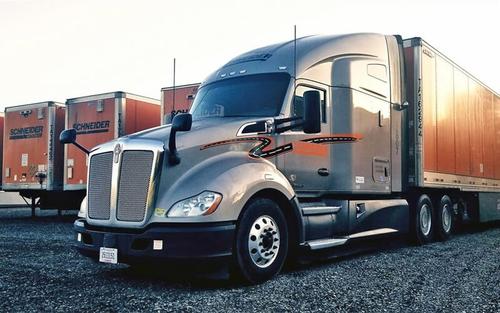 A grey Schneider Kenworth truck with an orange Schneider trailer is parked within a row of other orange Schneider trailers.