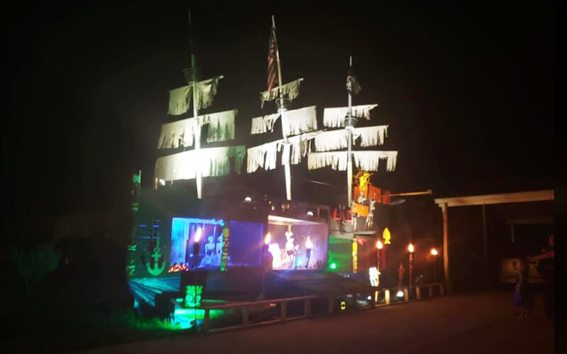 A giant handmade pirate ship sits on the edge of a driveway. The ship has three masts, color lights, skeletons playing instruments and an American flag.