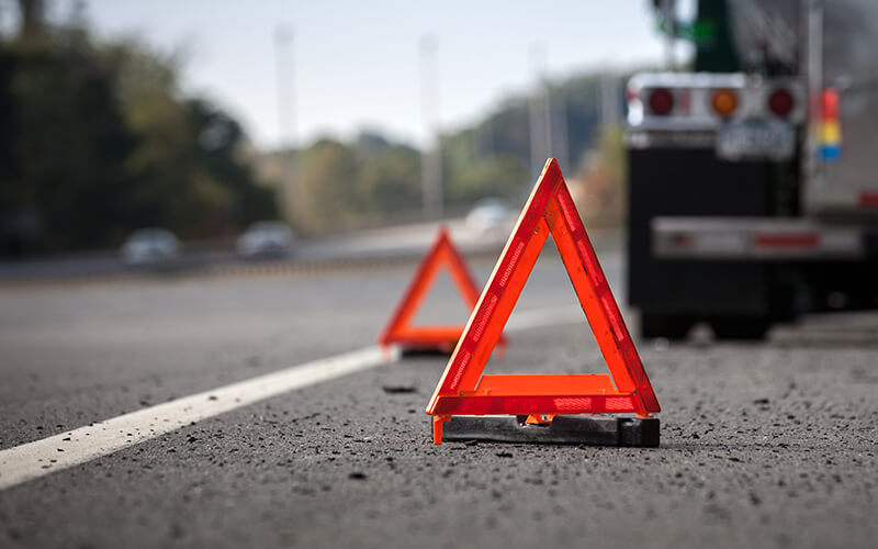 Two orange and reflective emergency triangles sit behind  truck that has pulled over to the shoulder of a highway.