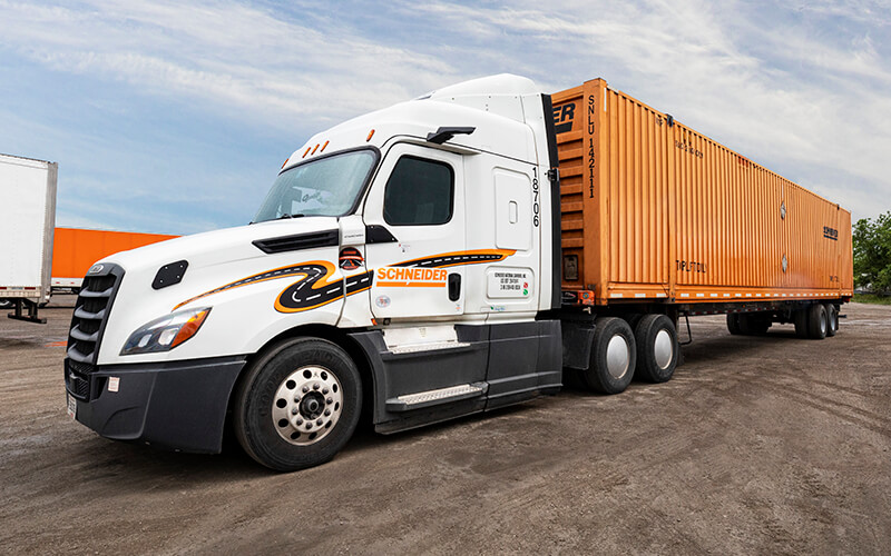 A white Schneider tractor with MirrorEye camera systems, carrying an orange intermodal container is parked at an angle in a dirt parking lot.