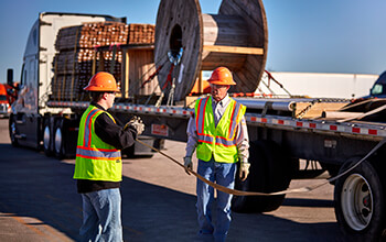 A truck driver trainer teaches a student how to secure a load.