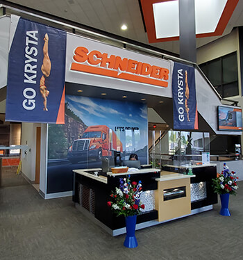 Posters of Krysta Palmer diving and red-white-and-blue flower pots decorate the front lobby of Schneider's headquarters.
