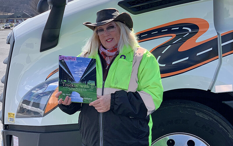 """JJ Artsy stands in front of her Schneider truck, wearing a safety jacket and hat, while holding her book, """"Truckin' with JJ."""""""