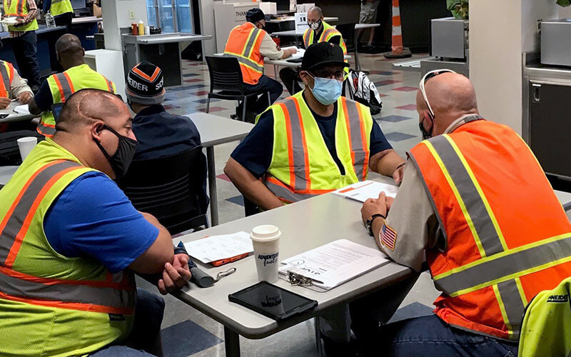 Three men wearing masks and safety vests, sit around a table with papers on it in a cafeteria and have a discussion.