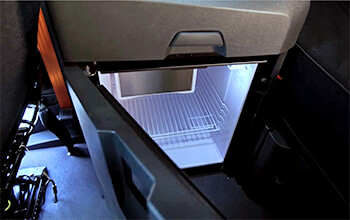 A grey mini-fridge is located behind the passenger seat on the inside of a semi-truck.