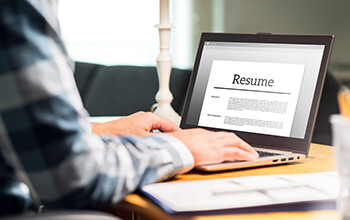 A person wearing a plaid shirt sits at a table and works on their resume on their laptop.