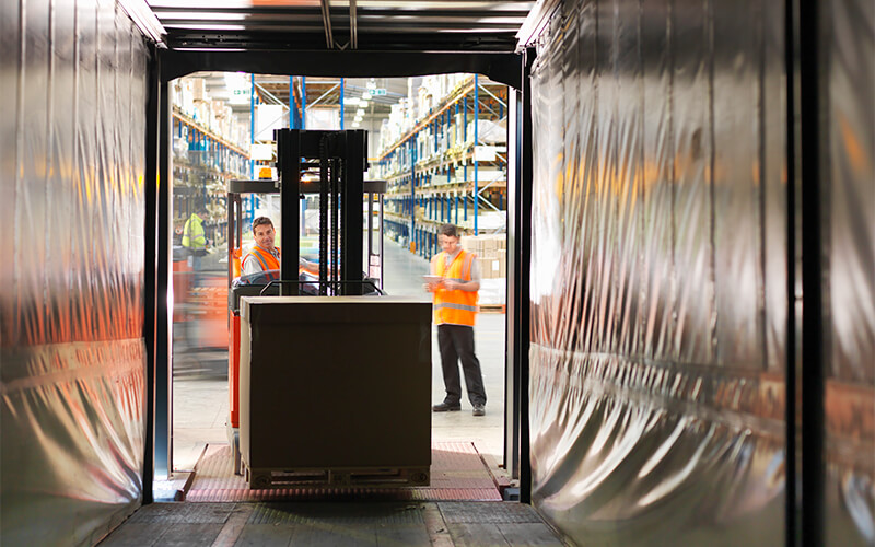 In a warehouse setting, while one warehouse associate takes a pallet off a semi-trailer using a forklift, another warehouse associate looks at a tablet.