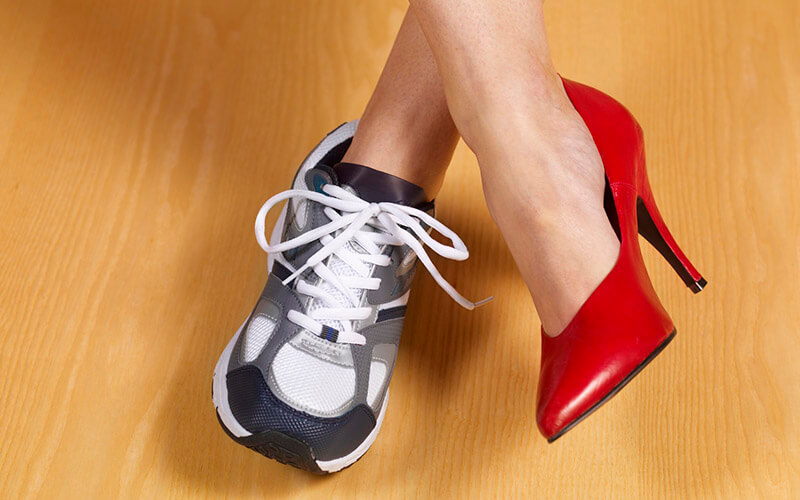 A woman wears a red high heel shoe on her right foot and a white and grey sneaker on her left foot, signifying the importance of balancing work and life.