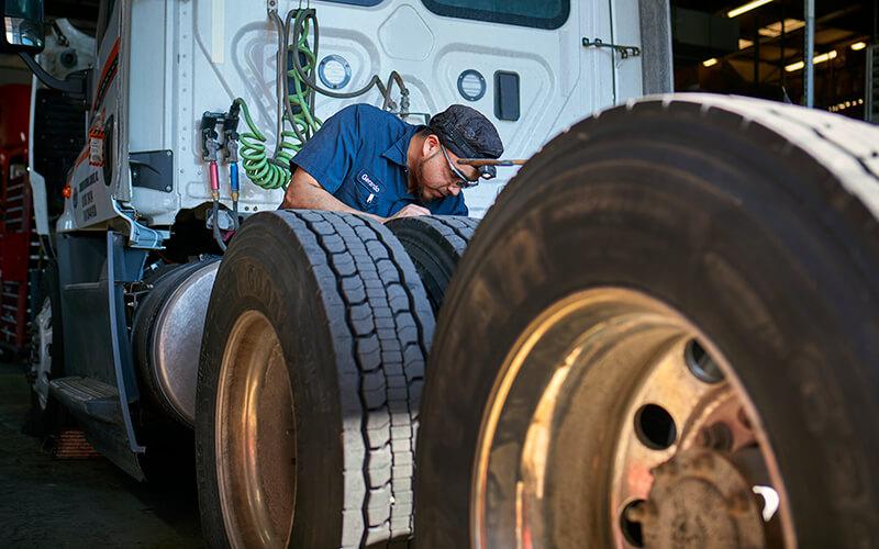 A Schneider diesel technician works on the backside of a white Schneider tractor.