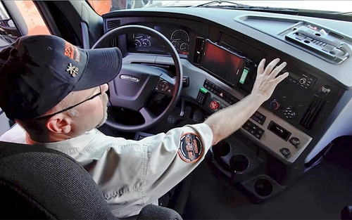 Driving Instructor Brett waves his hand in front of the dashboard of a 2021 Freightliner Cascadia semi-truck.