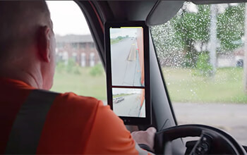 A man wearing a reflective orange shirt sits in the cab of a semi-truck and is looking at the MirrorEye monitors which are attached to the A pillar of the semi-truck.