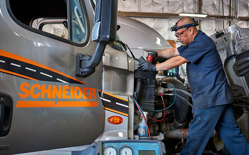 A Schneider diesel technician works on the front of a grey Schneider trailer in a shop.
