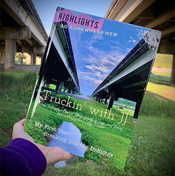 A hand holds JJ's book and on the cover of the book are two highways over a green marsh and a blue sky with white clouds.