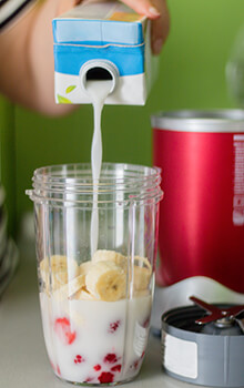 Someone pours milk into a personal blender containing strawberries and bananas.