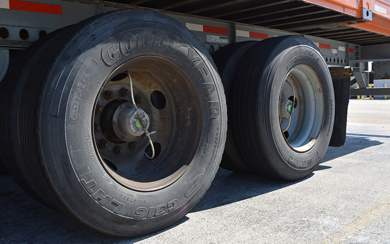 Four radial Good Year tires are attached to the back left-hand side of an Intermodal trailer. The thin tubes of the automatic tire inflation system come from the center of each tire hub and connect to the interior of the tire hub caps.