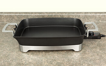 An empty black and stainless steel electric skillet sits on a counter.