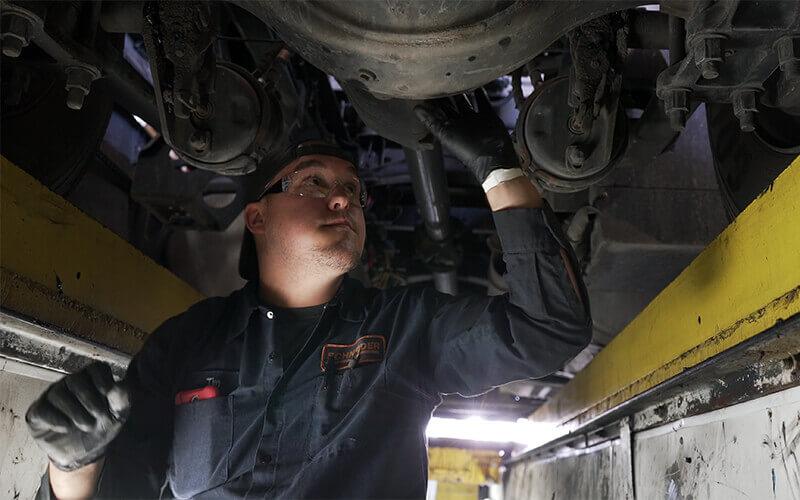 A Schneider diesel technician completes repairs to the underside of a Schneider truck.