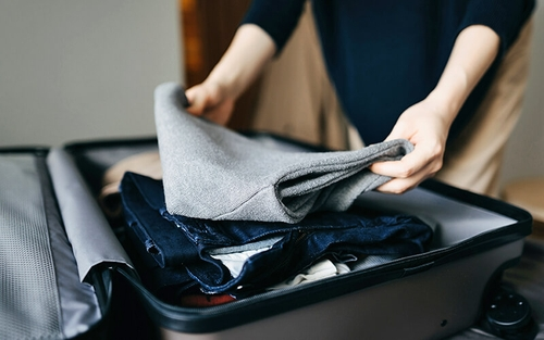 A man wearing khaki pants and a black long sleeve shirt packs a grey suitcase with various clothes, including a grey sweater and dark blue jeans.