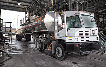 A white terminal tractor truck pulls a Tanker trailer into a shop.