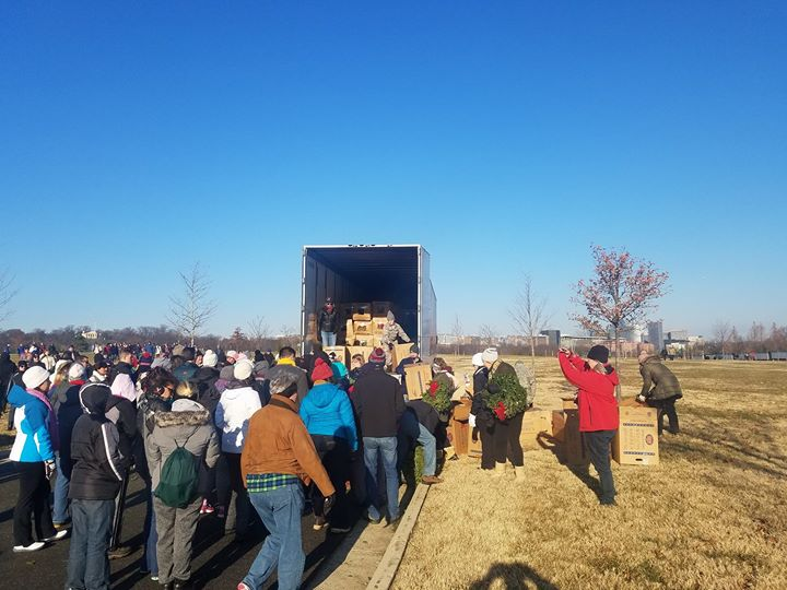Volunteers unload wreaths off of trailer for Wreaths Across America