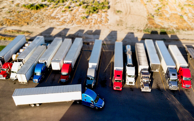 A variety of red, white, blue and silver semi-trucks hauling van trailers, flatbed trailers and tankers are parked side-by-side in semi-truck parking spaces. A blue truck hauling a white trailer appears to be lining up to back into a spot.