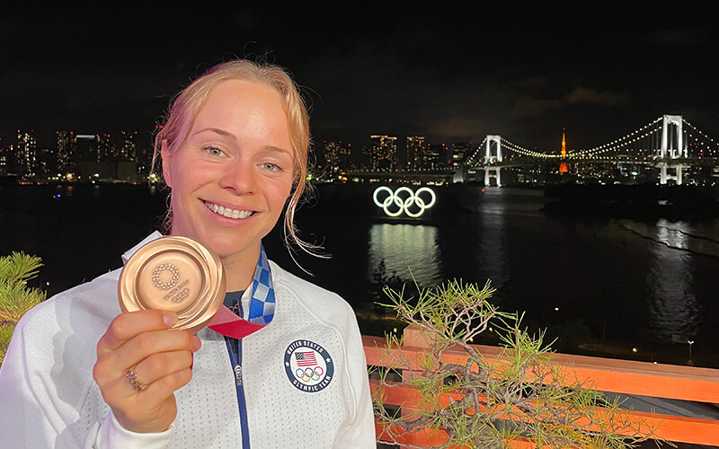 At night time, Krysta Palmer stands in front of a ridge in Tokyo and holds her bronze Olympic medal.