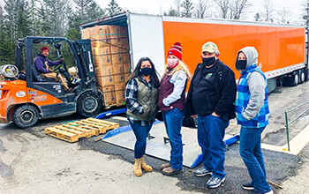 Three women and one man who are wearing masks, stand in front of a semi-trailer that is being loaded with boxes filled with wreathes.