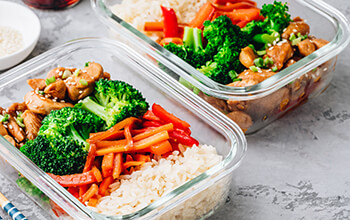 Two open reusable food containers hold a prepared meal of chicken, broccoli, peppers and rice.