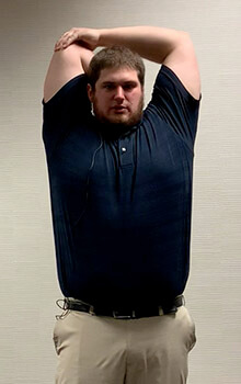 A physical therapist demonstrates stretching his elbow by bringing his arms overhead, grasping his elbow with the opposite arm and bending his elbow to reach down his back.