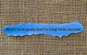 A scrap piece of blue paper has the saying, 'short term goals lead to long term success' in black lettering.