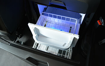A built-in refrigerator is open and shows food storage space in a sleeper cab.