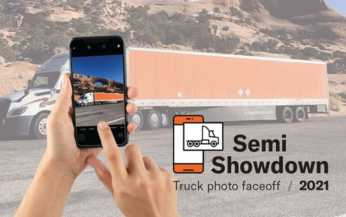 """A hand holding a phone takes a picture of a Schneider semi-truck. The bottom right corner says """"Semi Showdown truck photo face off 2021."""""""