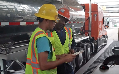 A Schneider tanker driver in a yellow hard hat and green safety vest talks with a Schneider diesel technician who is wearing a red hard hat and green safety vest.