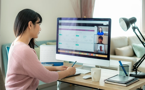 A young woman engages with her coworkers during a virtual meeting on the computer while she works from home.