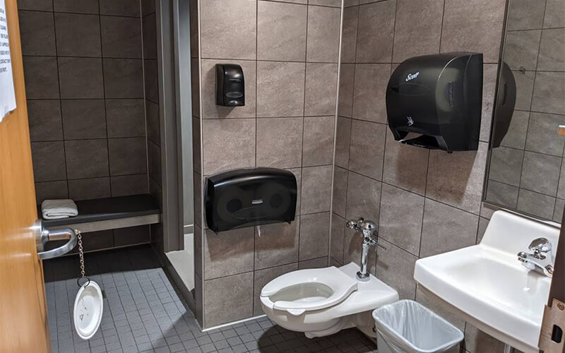 A bathroom stall at Schneider's facility in Dallas contains a shower stall, area to change, toilet, sink and mirror.