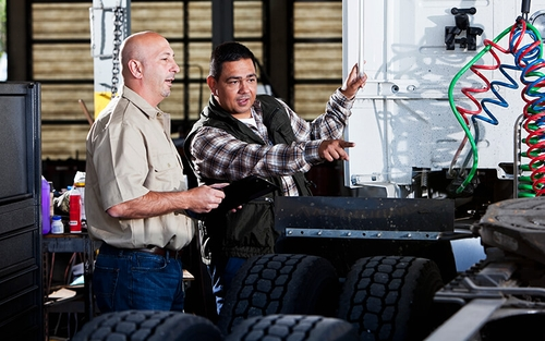 Two diesel technicians looking at the back of a semi tractor.